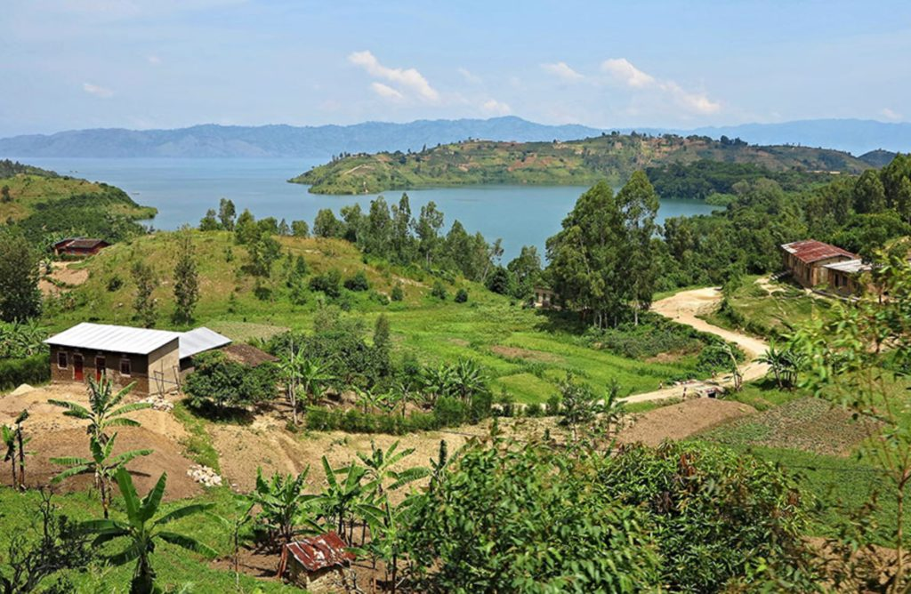 Image of rural Kinshasa, Congo. Image shows rolling green hills, the Congo River, and some small houses.