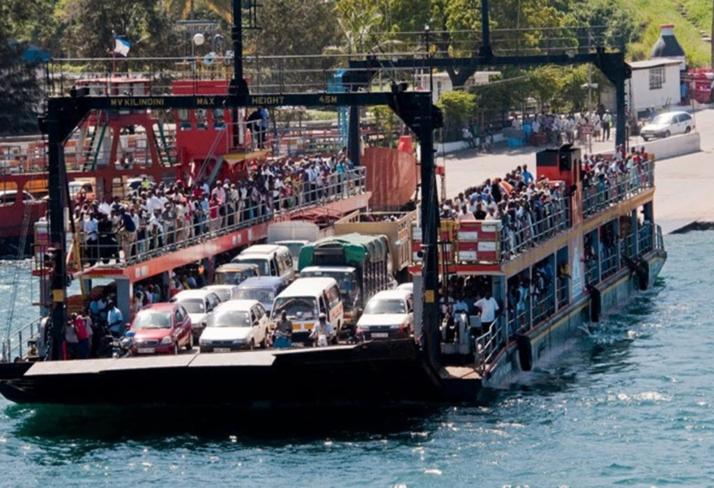 Image of Likoni Ferry in Mombasa, Kenya shows ferry with many people and cars leaving the dock.